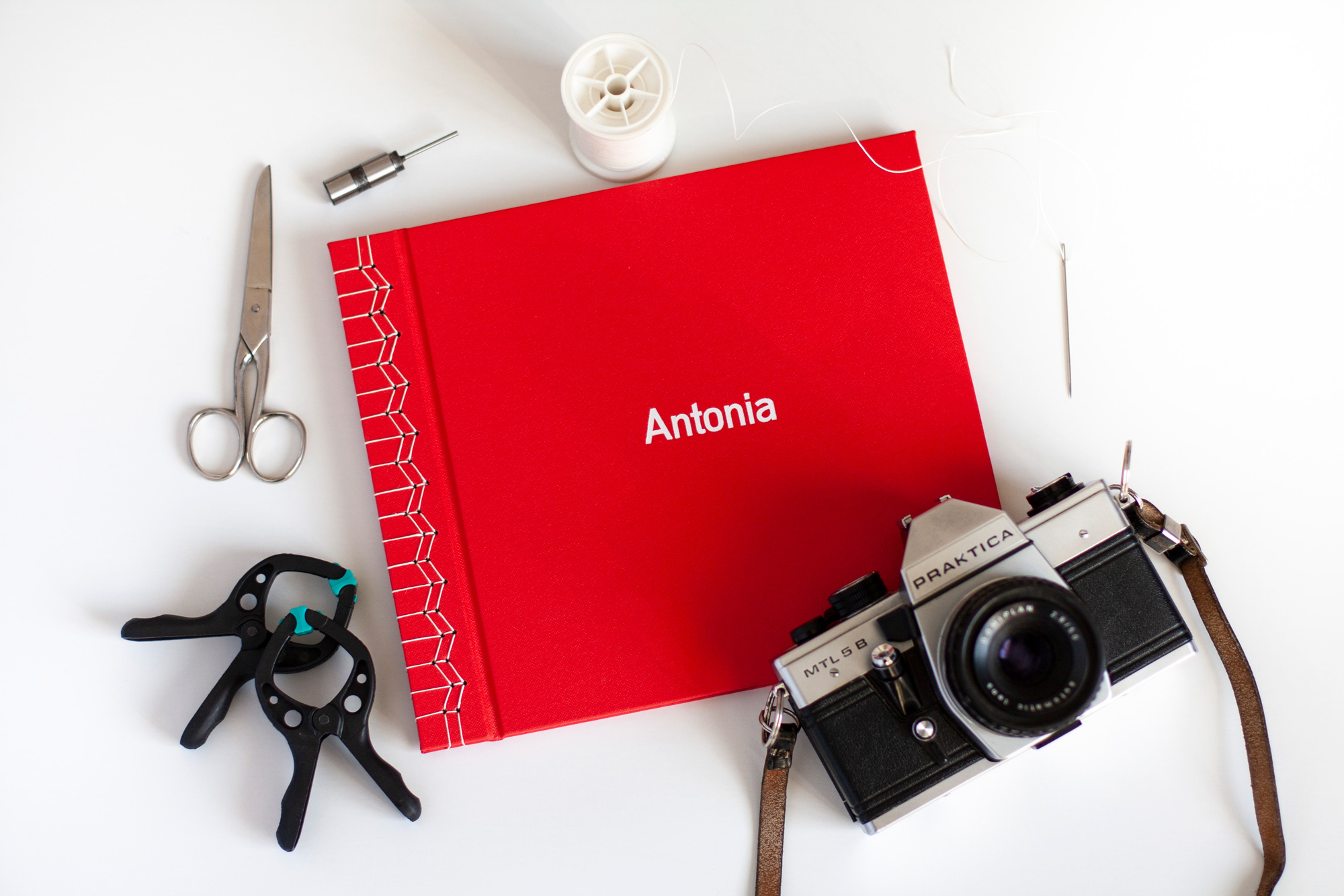 """Red Book With White Japanese Stab Stitch Binding And White Hotfoil Stamp In Center """"Antonia"""", Flatlay On White Background With Bookbinding Props And Analog Camera"""
