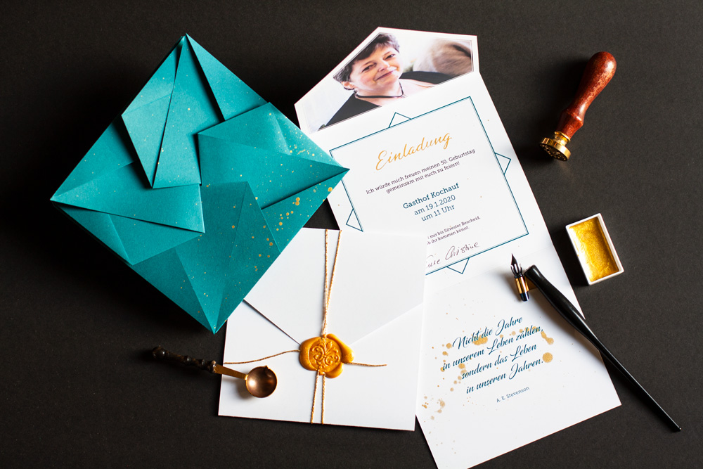 Flatlay Of An Invitation For 50s Birthday, Blue-green Origami Envelope With Gold Splashes On Black Background, Invitation Card Secured With Gold String And Golden Wax Seal, Fold-out Invitation With Picture On Top, Invitation Text In The Center Including A Handwritten Headline In Gold Written In Pointed Pen Modern Calligraphy And A Quote Of Adlai Ewing Stevenson At The Bottom Also In A Modern Calligraphy Font, Finished With Gold Splashes. Used Props Are The Wax Seal Stamp, A Wax Seal Spoon, The Pointed Pen Holder With Steno Nib And The Tray Of Golden Watercolor Which Was Used For The Calligraphy And Splashes
