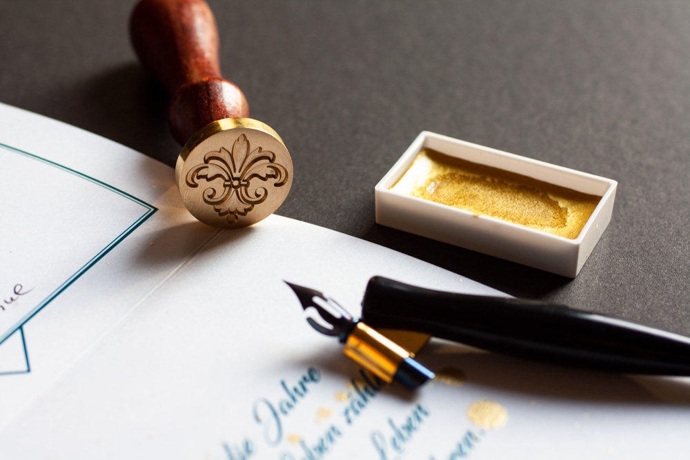 Details Of The Used Tools That Are Also Used As Props For The Flatlay: Wax Seal Stamp, Nib Holder With Steno Nib, Gold Ink
