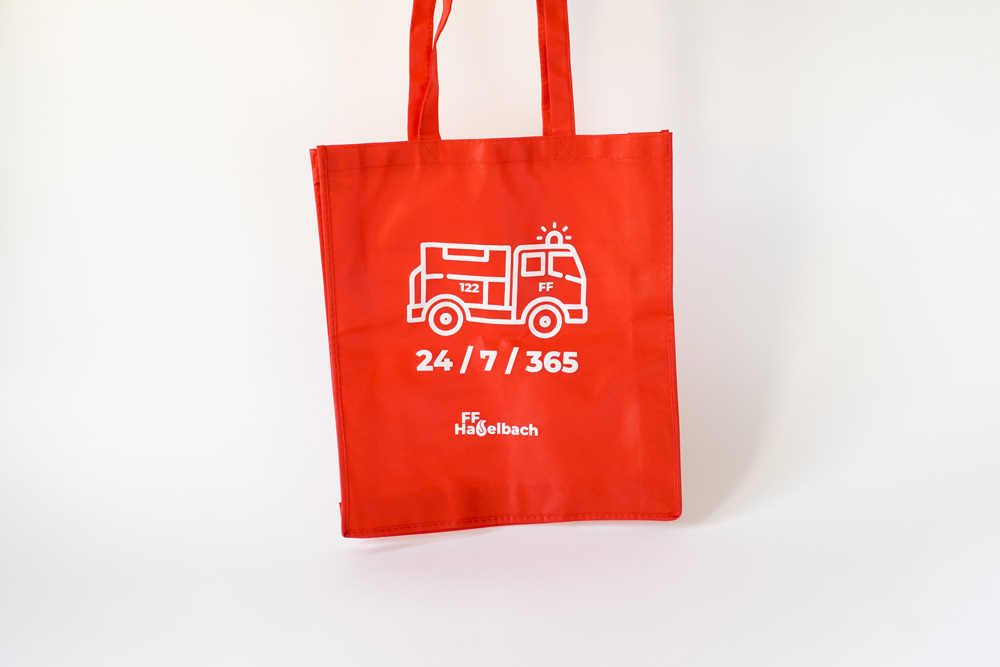 "Front Side Of The Bag With A Fire Truck And ""24 / 7 / 365"" And The Logo"
