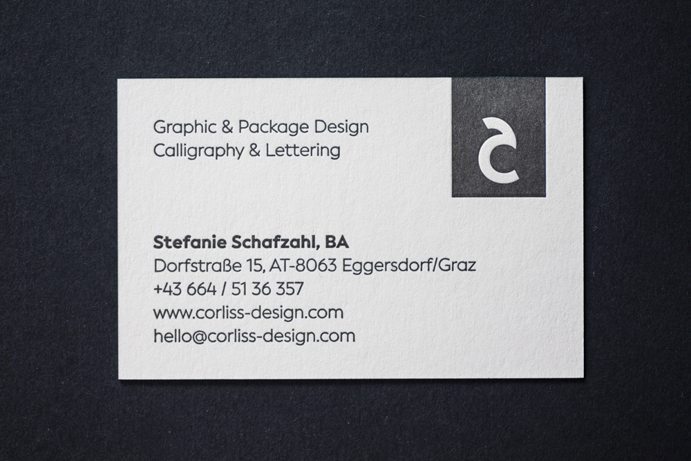 Corporate Design And Branding For Corliss Design, Here The Back Side Of The Business Cards Are Shown: Logo In Black Letterpressed On The Front Side, Top Left Scope Of Action, Bottom Left Contact Details, Top Right Logo, On Cream Colored Paper