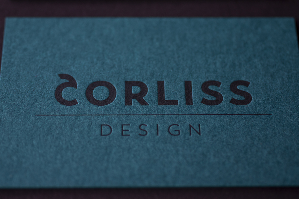 Corporate Design And Branding For Corliss Design, Here The Business Cards Are Shown: Logo In Black Letterpressed On The Front Side, Here On Dark Petrol Paper