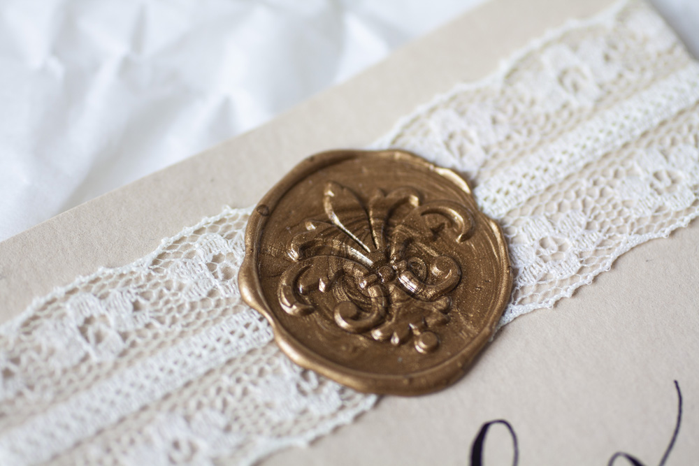 Modern Calligraphy Place Card With Black Ink On Cream Colored Paper, White With Delicate Lace, Close Up Of Bronze Wax Seal