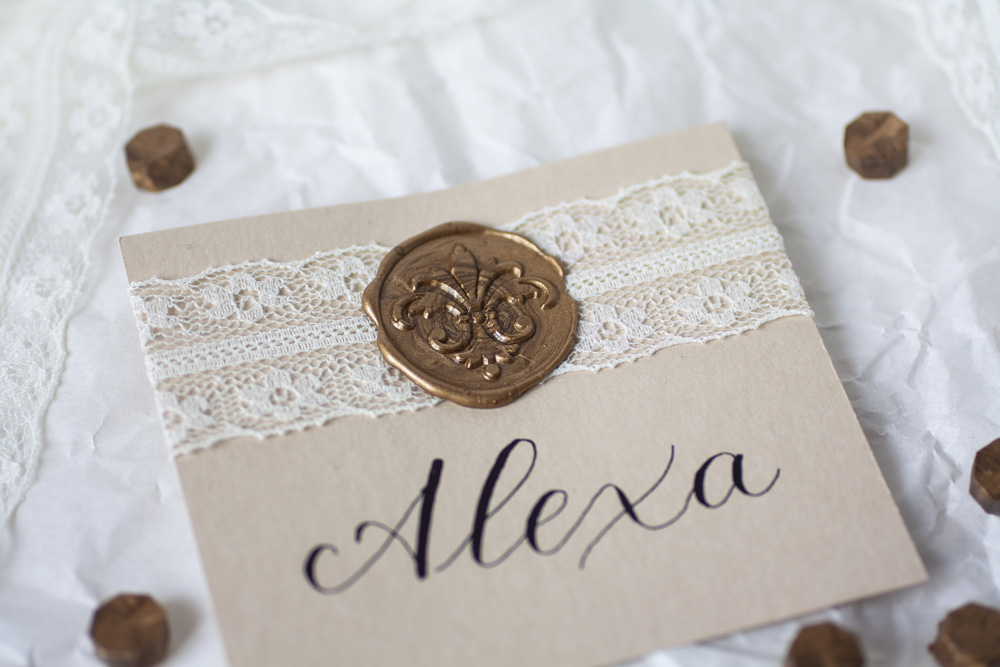 Modern Calligraphy Place Card With Black Ink On Cream Colored Paper, White With Delicate Lace And Bronze Wax Seal, Focus On Wax Seal