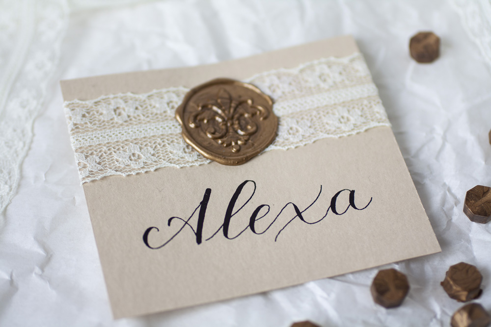 Modern Calligraphy Place Card With Black Ink On Cream Colored Paper, White With Delicate Lace And Bronze Wax Seal, Focus On Calligraphy